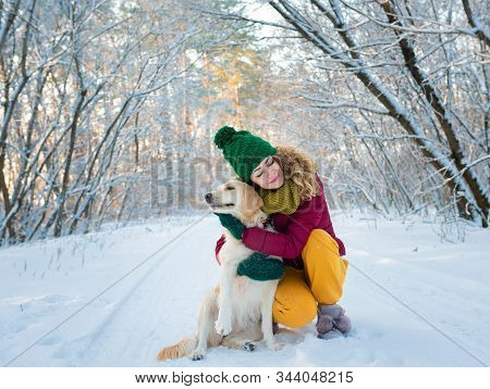 Smiling Woman Hugging Her Pet Dog Golden Retriever Near Face. Golden Retriever Playing With A Woman