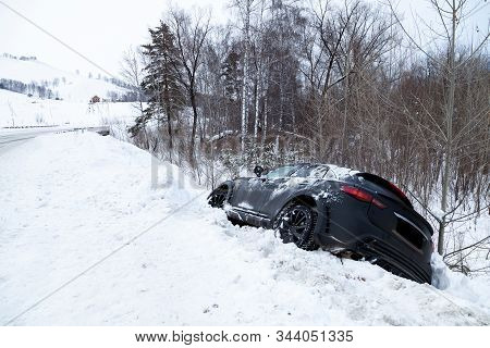 Accident On A Winter Snowy Track With A Black Car Skidding And Falling Into A Ditch Due To Ice. Safe