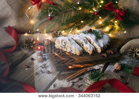 Homemade Traditional Dessert Stollen With Powdered Sugar Stands On Wooden Board With Decoration And