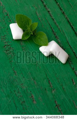 Group Of White Cubes Of Mint Chewing Gums With Fresh Peppermint Leaves On Dark Green Wooden Backgrou