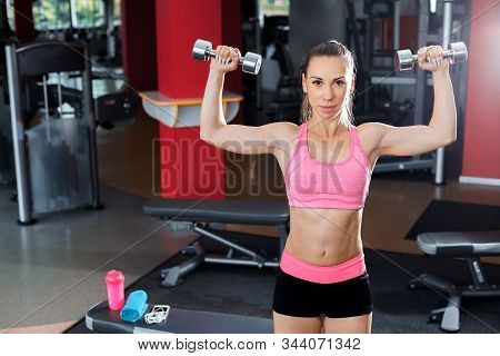 Athletic Pretty Woman Wearing Pink And Black Professional Sportswear Lifting Dumbbells In A Gym. Fit