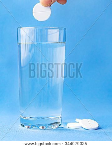 Fizzy Aspirin In A Glass Of Water On A Blue Background. Vertical Format And Soft Focus.