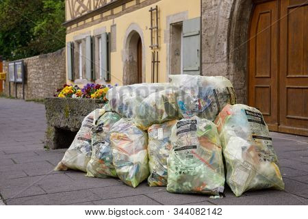 Rothenburg ob der Tauber, Germany - May 9, 2019: Pile of yellowish Wertstoffsack garbage bags overfilled with recyclable plastic and cardboard trash awaiting collection
