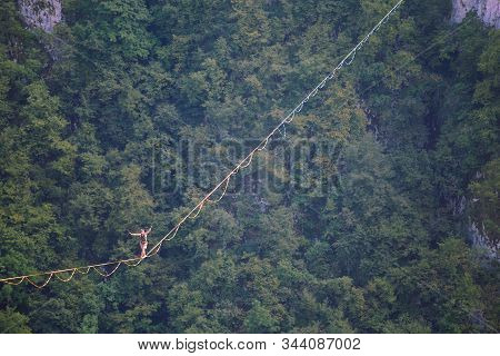 Highline In The Mountains. A Man Goes On A Stretched Sling. Highline Is On The Line. A Tightrope Wal