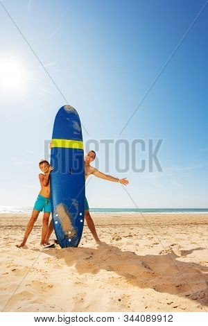 Father And Son Behind Surf Board On The Sand Beach