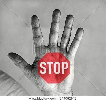 Men`s Palm With A Stop Sign. Red Hexagon And White Stop Sign.man Holds Palm In Front Of Him. He Has
