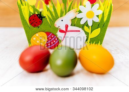 Closeup Of Three Blurred Colourful Easter Eggs In Front Of Decorative Felt Basket On White Painted V