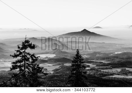 Ralsko Mountain Rising From The Mist. Weather Temperature Inversion In Central Bohemian Uplands, Cze