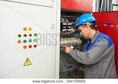 electricianat work in electric distribution switching cabinet