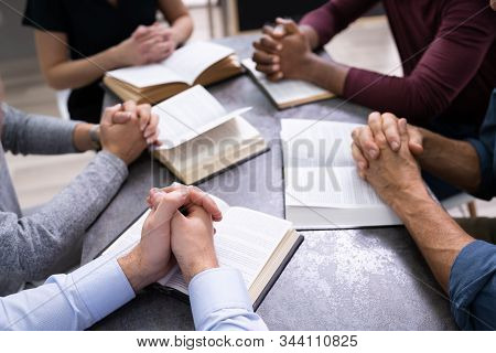 Elevated View Of People Reading Holy Books On Wooden Background