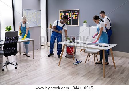 Group Of Janitors In Uniform Cleaning The Office With Cleaning Equipment