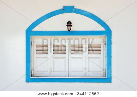 White Window Shutters With Light Blue Strip Around It. Exterior In Details. Closed Windows With Whit