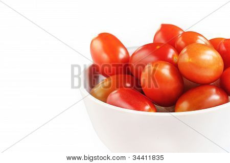 Group Of Fully Ripe Organic Cherry Tomatoes In Bright Red Color Arranged In A White Melamine Bowl On