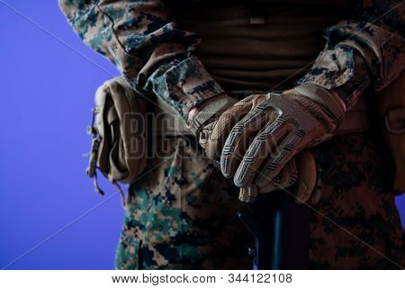 american  marine corps special operations modern warfare soldier with fire arm weapon and protective army tactical gear ready for battle on purple background