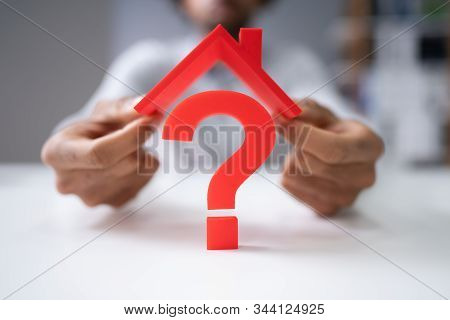 Man's Hand Holding Roof Over Question Mark Sign