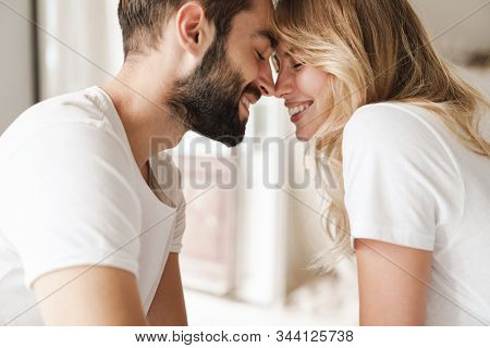 Beautiful happy young couple relaxing on bed at home, embracing