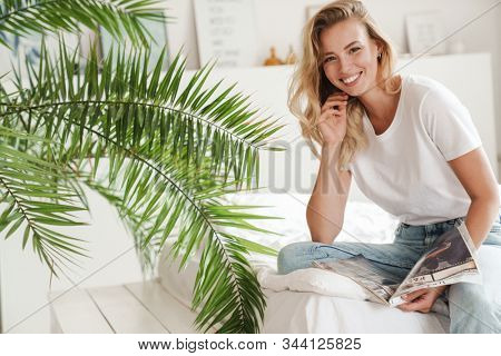 Smiling young beautiful woman reading magazine while sitting on a couch at the living room