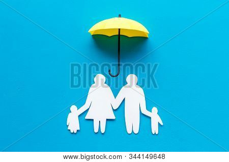 Health Insurance Concept. Family Cutout Under Umbrella On Blue Background Top-down Copy Space