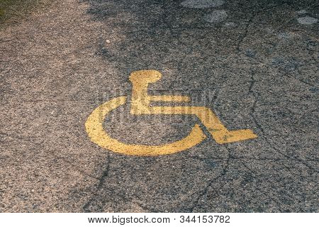 Yellow Handicapped Symbol Of Wheelchair Painted On Asphalt On A Parking Lot, Sign Of Parking Space F
