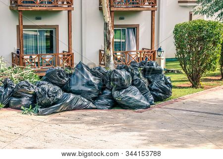 Pile Of Black Garbage In Bags Near The Road In The City, Pollution Trash. Black Garbage Bag, Plastic