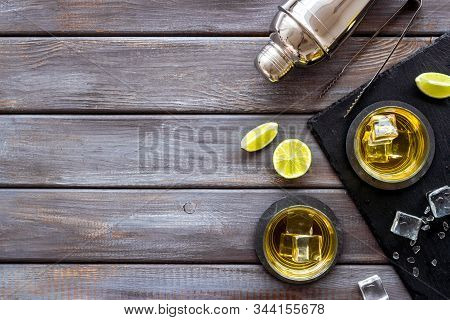 Bar Background With Whiskey, Ice And Shaker On Dark Wooden Desk Top-down Frame Copy Space