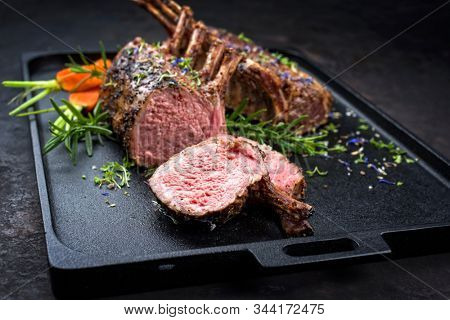 Barbecue rack of lamb with carrot and herbs offered as closeup on a modern design cast iron tray
