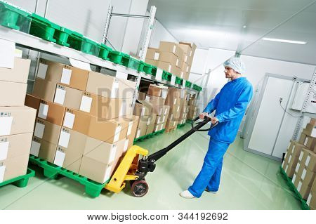 medical warehouse worker with manual lift loader