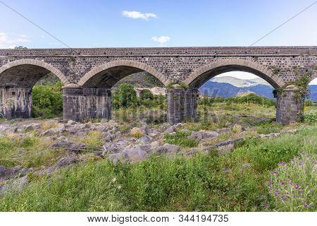 Old Stone Bridge Over River Alcantara Near Castiglione Di Sicilia Village, Sicily In Italy