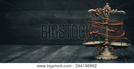 Scales Of Justice And Barbed Wire On A Black Wooden Background, Compromised Rule Of Law, Weakness Of