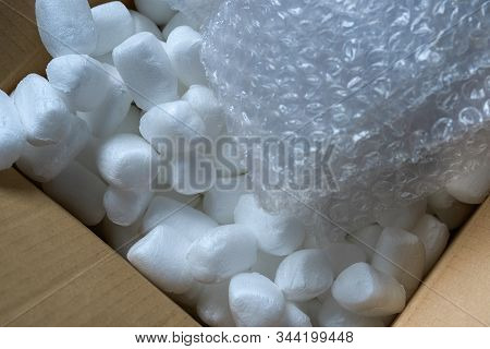 Modern Packaging Materials Are Bubble Wrap And Pieces Of Foam Filling In An Open Cardboard Box.