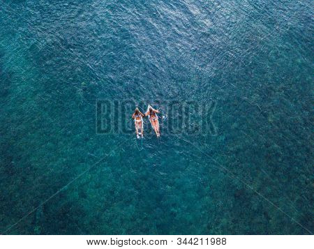 Two girls paddle side by side in the ocean, top to down aerial shot of surfing
