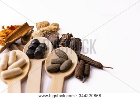 High Angle Close-up Shot Of Ayurvedic Tablets And Capsules In Three Wooden Spoons With Assorted Indi