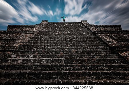 A Traveler Standing On The Top Of The Teotihuacan Pyramid. Time-lapse Sky Shows The Concept Of Centu