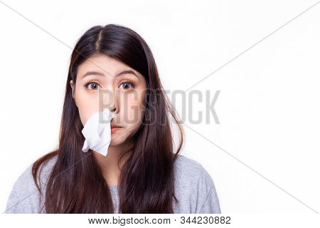 Asian Woman Put Tissue Paper In Her Nose. She Have A Stuffed Nose Or Runny Nose. Pretty Girl Has A C