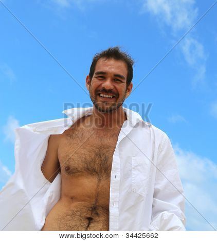 Smiling Male With Shirt Open And Blue Sky Behind Him