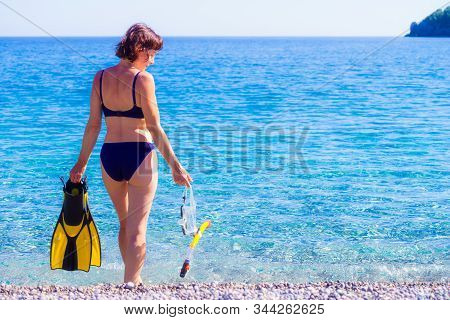 Mature Female With Snorkel Equipment Flippers And Snorkeling Mask Tube On Beach Sea Shore. Summer Va