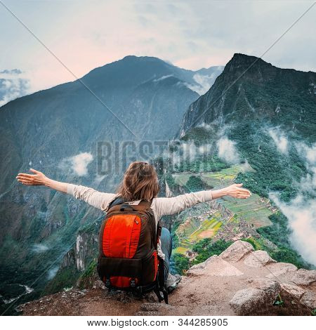 View of girl sitting on the edge of the rock with raised hands and taking pleasure of breathtaking forested mountains landscape of Machu Picchu