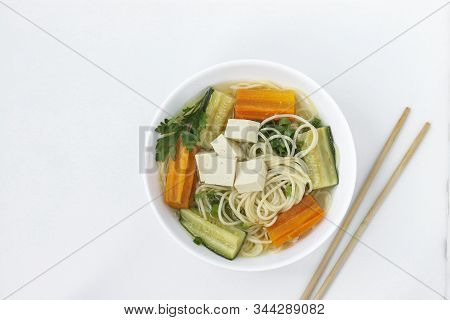 Traditional Asian Soup With Tofu Cheese, Noodles, Carrots And Zucchini On White Background, Dish Usu