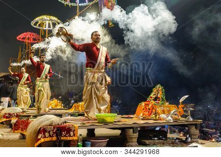 VARANASI, INDIA, JANUARY 17, 2019 : Hindu priests are waving incense cups during the Ganga Aarti ceremony along the river bank