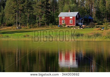 Small Red Swedish Old Two-storey Residential One Family Building Built Of Wood Next To The Lake Is R