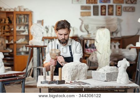 Male Sculptor In White Shirt And Black Apron Makes A Limestone Copy Of Woman Torso At The Artistic S