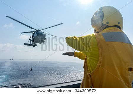 Chonburi, Thailand - December 24, 2019 : Helicopter Deck Officer Give Hand Signal To Sikorsky S-70 S