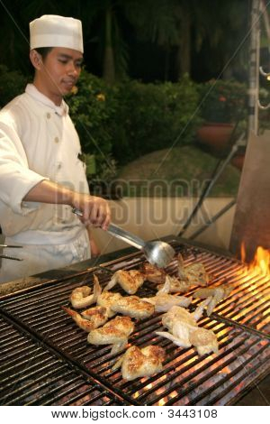 Chef Grilling Chicken Wing In Bbq