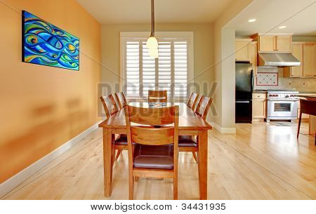 Orange Dining Room With Hardwood Floor And Kitchen.