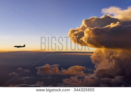 A Storm Front At Sunset With An Airplane In Front Of The Storm