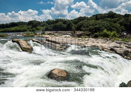 Fast River Flowing On Bedrock In Front Of Green Forest Under Sky