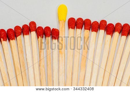 One Single Yellow Tipped Matchstick Laying In Middle Of Many Red Tipped Matchsticks