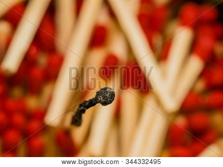 One Single Burnt Matchstick Standing In Middle Of Many Blurred Out Red Tipped Matchsticks