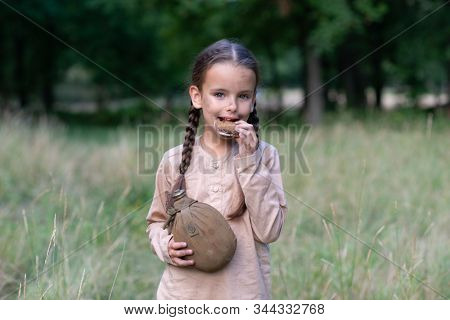 Pretty little girl with long pigtails and beautiful dirty face sitting walking in summer forest holding a piece of stale bread and vintage flask. Orphan, child of war, poverty, hunger, famine, poor