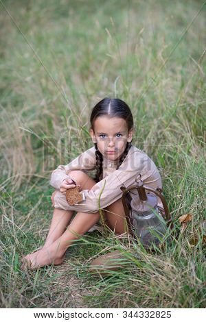 Pretty little girl with long pigtails and beautiful dirty face sitting at summer meadow with vintage paraffin stove and stale bread. Orphan, child of war, poverty, hunger, famine, poor destitute kid.
